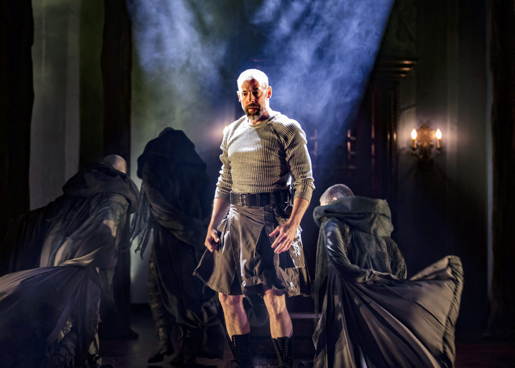 Macbeth (played by Ian Merrill Peakes) stands surrounded by the Three Weird Sisters