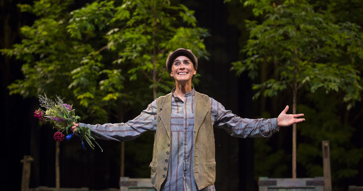 "Photo: Rosalind stands alone onstange with her arms outstretched in ""As You Like It."""