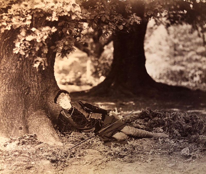 Photograph of a woman lounging under a tree