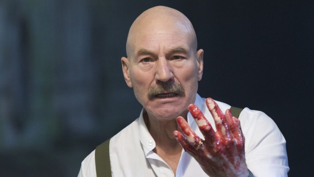 Patrick Stewart, as Macbeth, stares at his blood-covered hand.